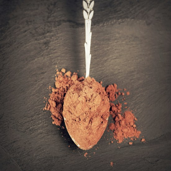 Cocoa Powder In Spoon On Black Slate Background