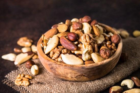 Assortment Of Nuts In Wooden Bowl. Cashew, Hazelnuts, Walnuts, A