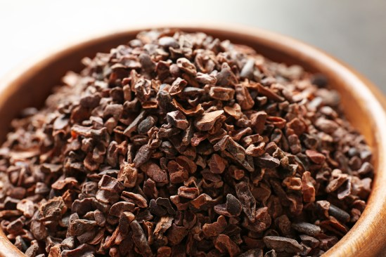 Bowl with aromatic cocoa nibs, closeup
