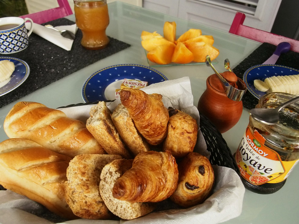 Assortment of warm pastries with jam and butter. Banana, Persimmon. Capuccino, hot tea.