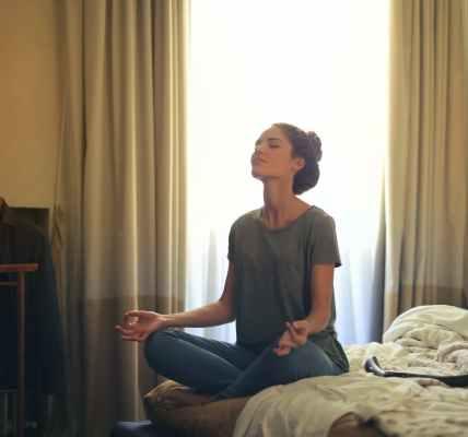 woman meditating in bedroom