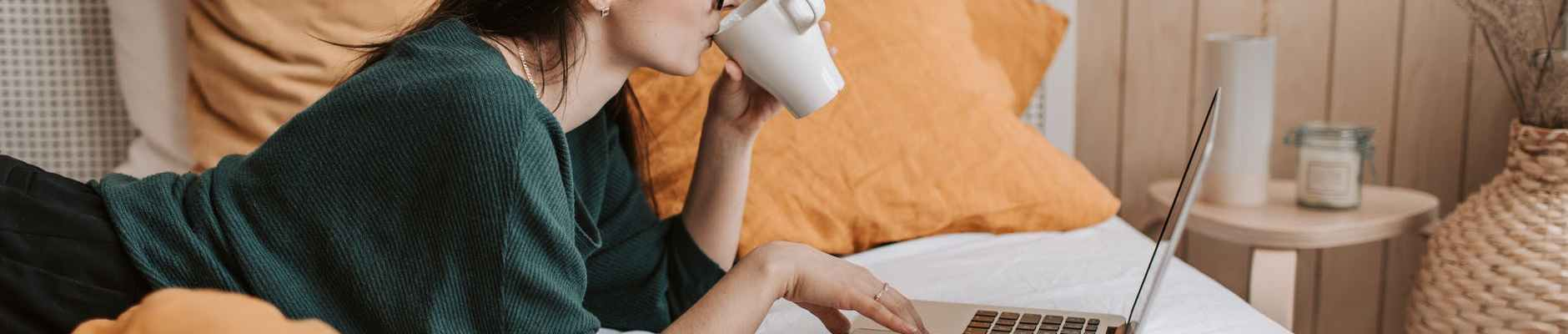 woman using laptop and drinking beverage in bed