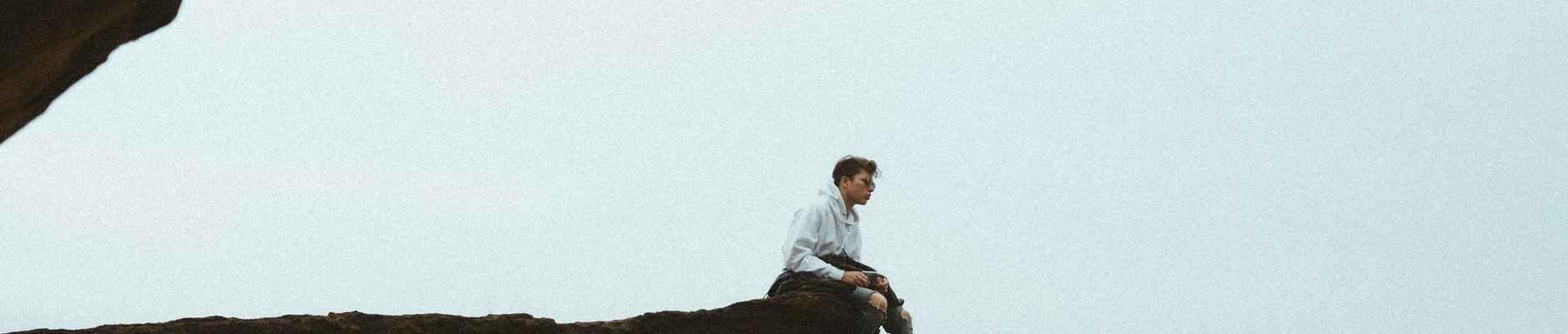 calm man on edge of cliff above ocean
