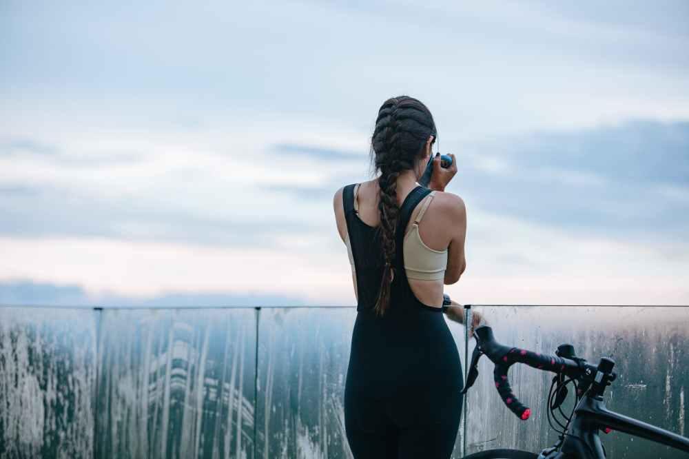 faceless female bicyclist drinking near bike under cloudy sky