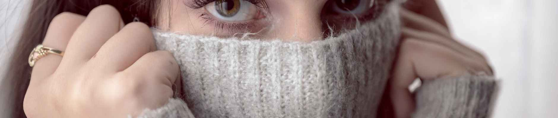 woman covering her face with gray knit textile