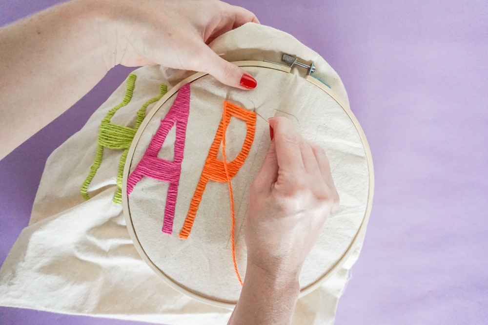 a close up of doing Yarn Embroidery: How to Embroider Letters (A HAPPY DIY Tote Bag)