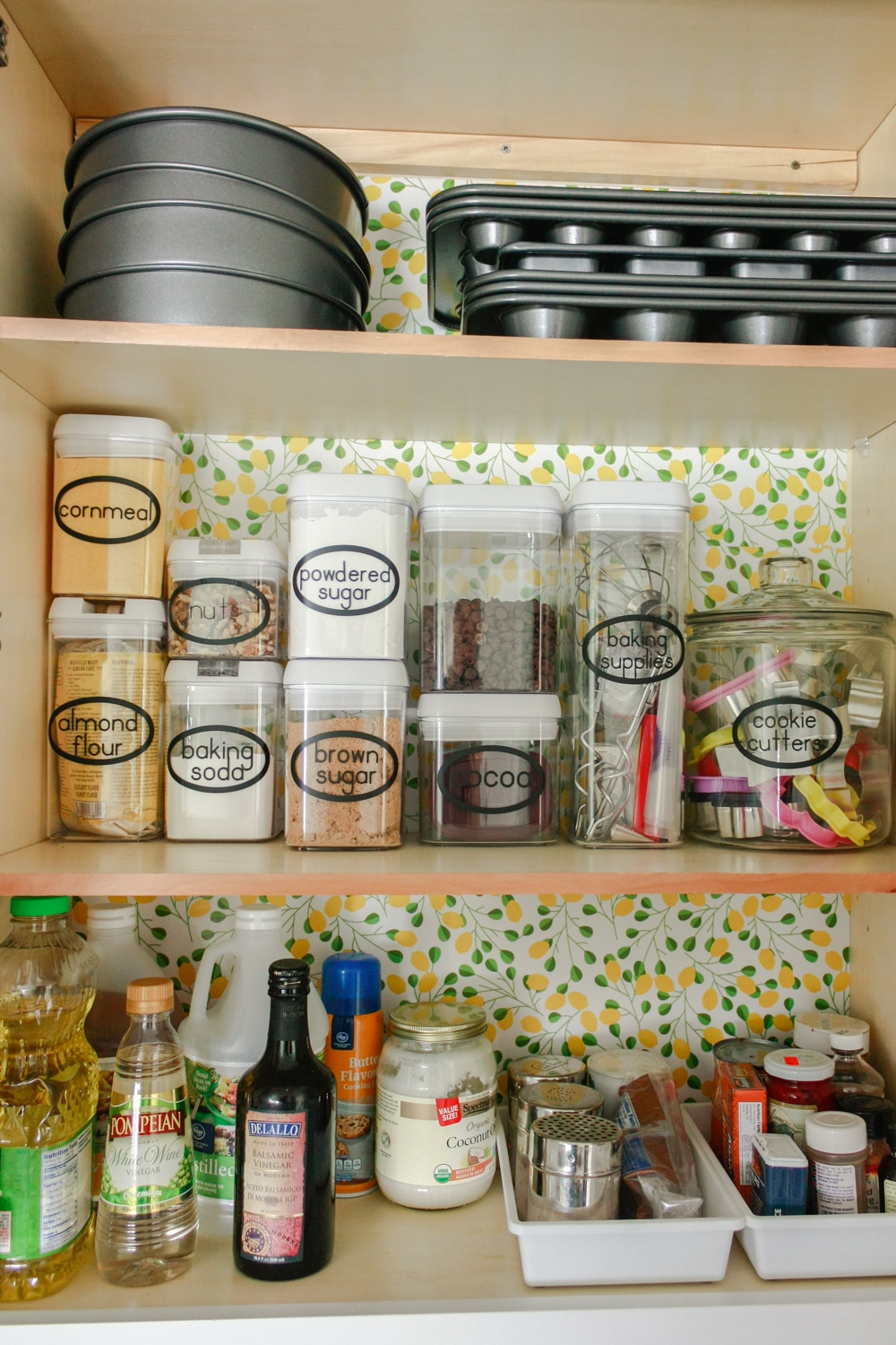 Organizing baking supplies is easy with cork tiles, command hooks, vinyl labels, and a beautiful craft paper to line the cabinet.