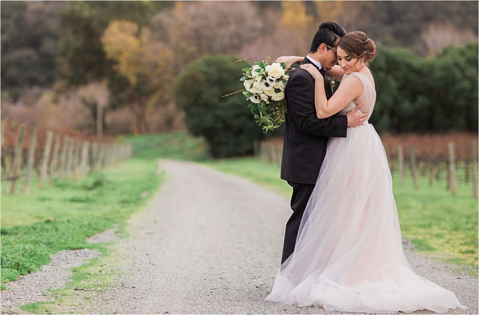 Bride and groom embracing on a dirt road lined by vineyards.
