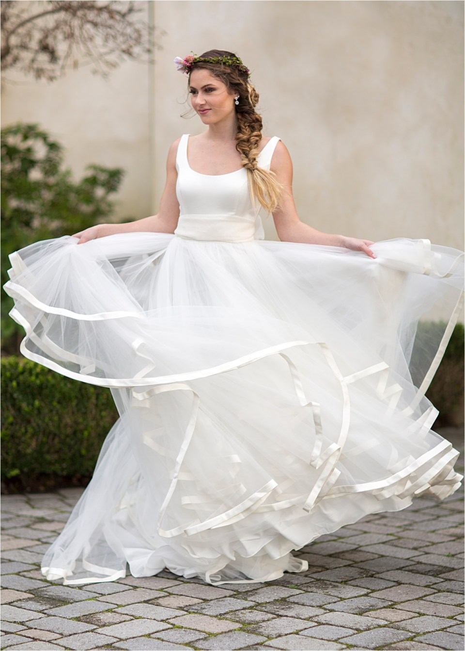 Bride twirling in a sleeveless ivory WattersWtoo gown.