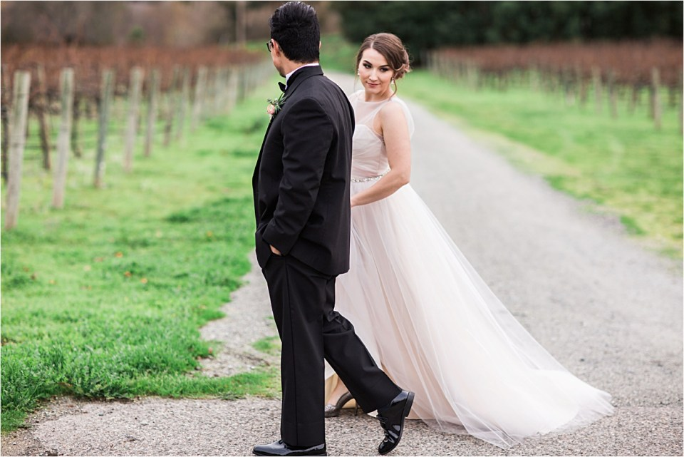 Bride in a blush Hayley Paige gown walking with her groom and looking over her shoulder.