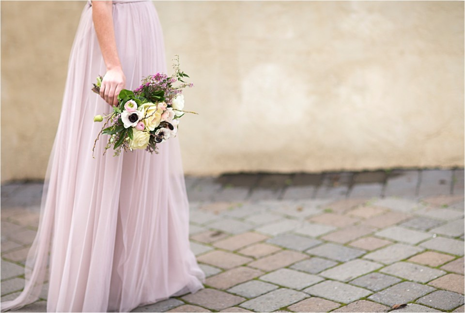 Bridesmaid in a lavender WattersWtoo gown walking on cobblestone