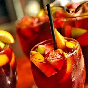 un verre de sangria rempli de morceaux de fruit et avec une paille