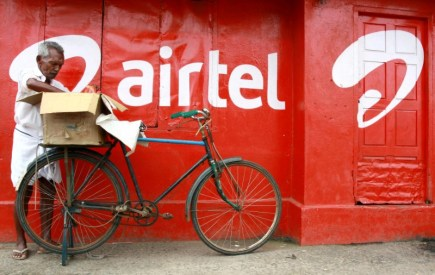 FILE PHOTO: A man stands next to the wall of a grocery shop painted with an advertisement for Bharti Airtel in Kochi
