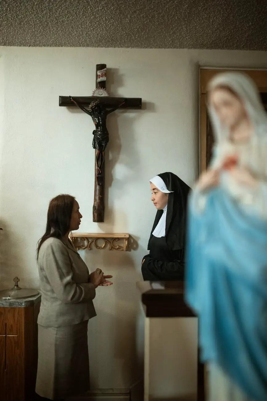 woman in blue dress standing beside woman in white hijab