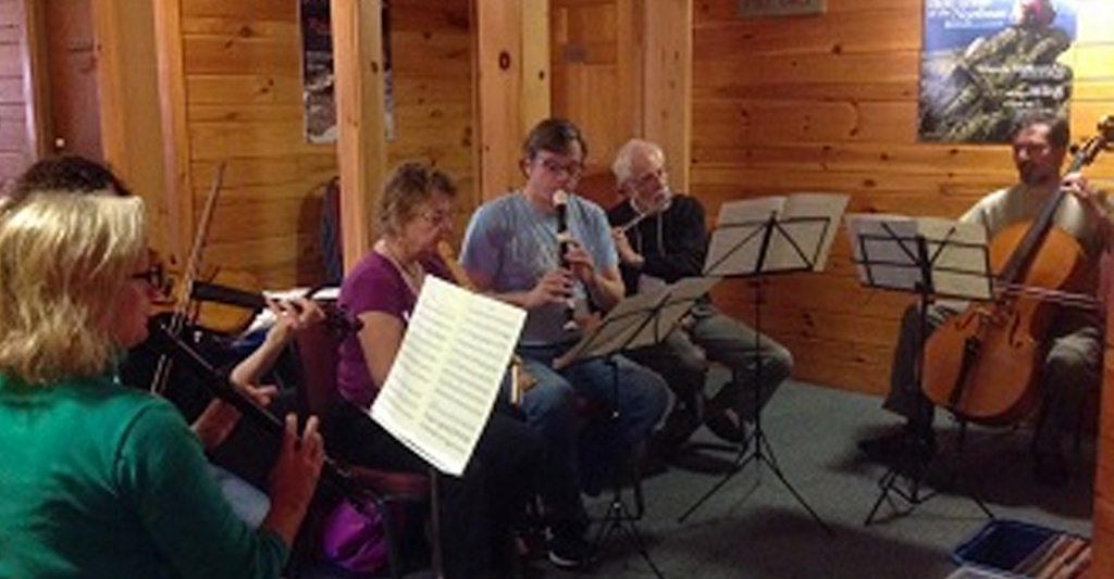 musicians gathered in a circle, seated, playing instruments