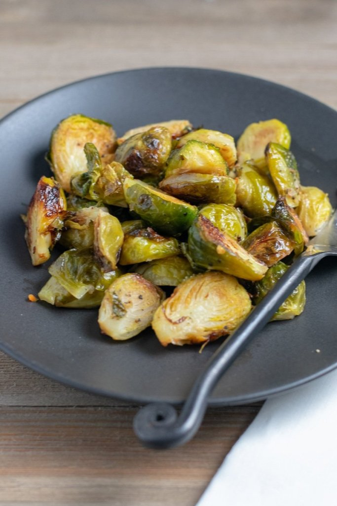 Baked brussels sprouts on a black plate