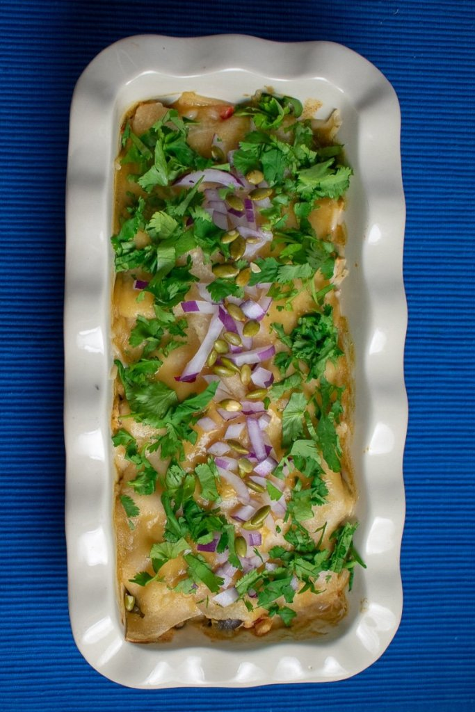 easy layered green chile chicken enchiladas in fluted baking dish with cilantro and onion garnish