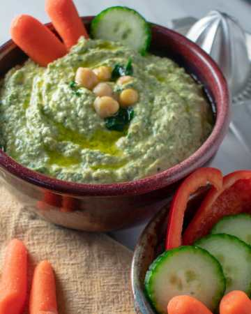 Garlicky spinach artichoke hummus in red bowl overhead view