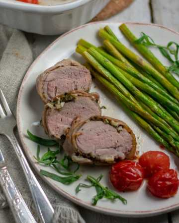 Pork tenderloin with bacon and veg on white plate