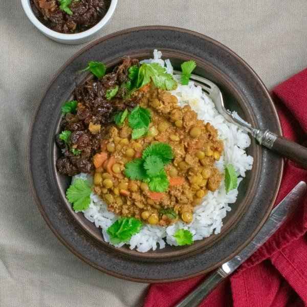 Spiced Lentils with Beef in brown bowl with raisin chutney