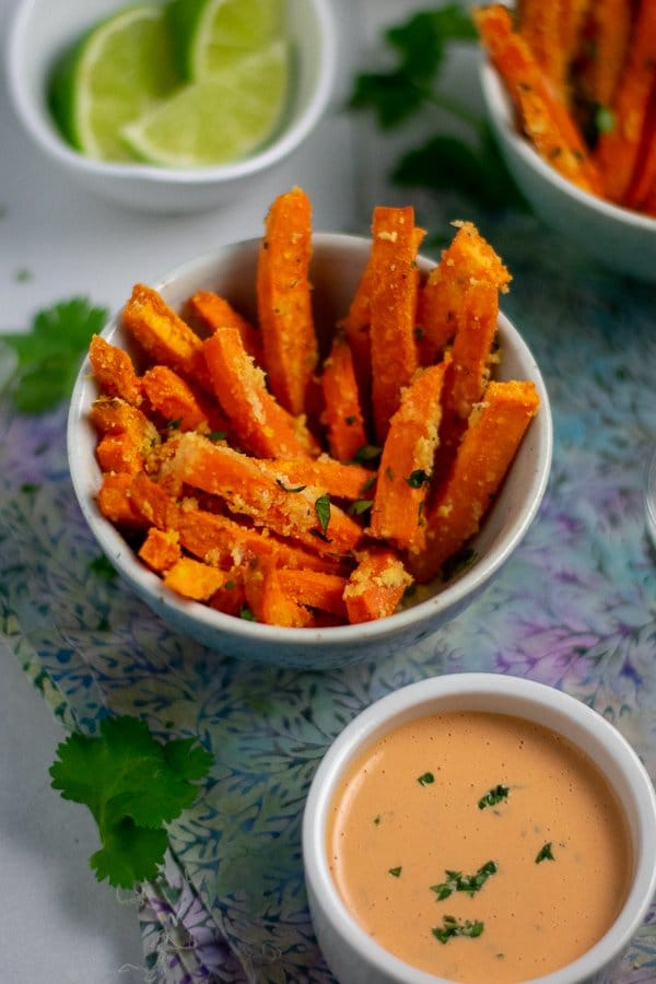 Roasted Sweet potato fries and sriracha mayo in small bowls with limes