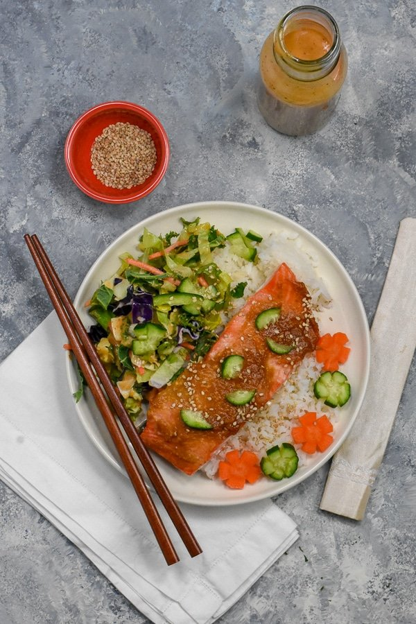 miso salmon fillet on white rice with salad on white plate with chopsticks