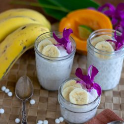 coconut milk tapioca pudding in glass jars garnished with bananas and orchids