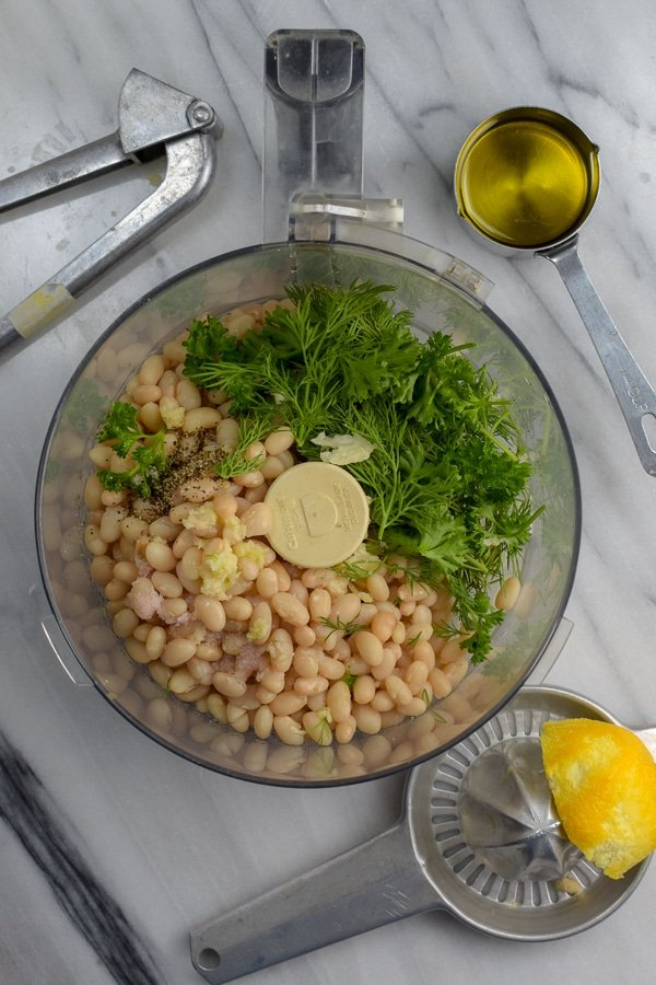 ingredients for white bean lemon dill dip in food processor with tools nearby