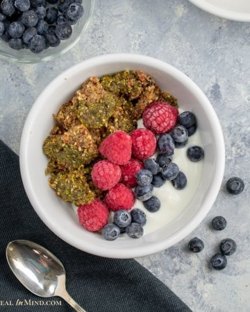 moringa fruit-nut-ola in white bowl with berries and kefir