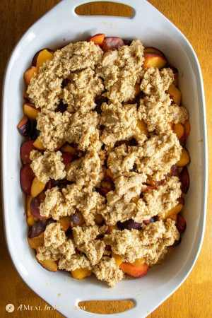 easy mouthwatering peach-plum cobbler in ceramic baking pan before baking