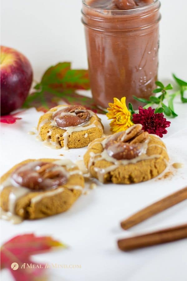 delicious pumpkin cookies with apple butter thumbprint with jar of apple butter closeup