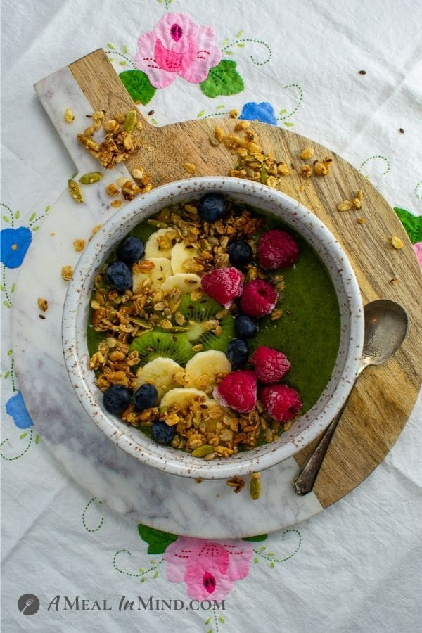 Chia-Greens Peach Smoothie Bowl with fruit garnishes on marble-wood board