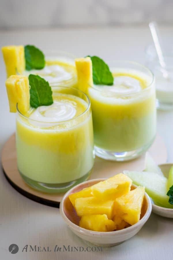 Layered Pineapple-Honeydew Lassi with pineapple and mint garnish