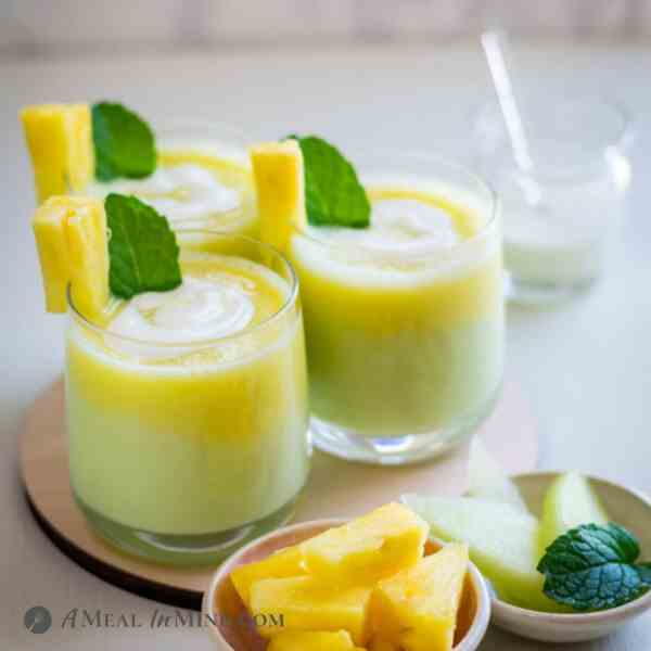 Layered Pineapple-Honeydew Lassi in three clear glasses with pineapple garnish