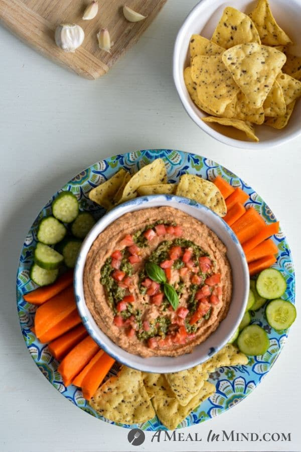 Tomato-Pesto Hummus in blue and white bowl on blue patterned plate