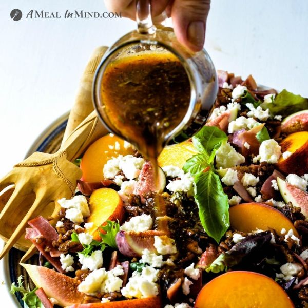 Fig-Peach Pecan Salad with Feta and Balsamic Vinaigrette square image of dressing poured onto salad