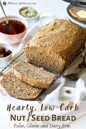 Loaf of low carb nut and seed bread sliced on cooling rack