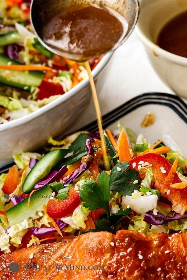 pouring tangy ginger-almond dressing onto asian slaw on plate