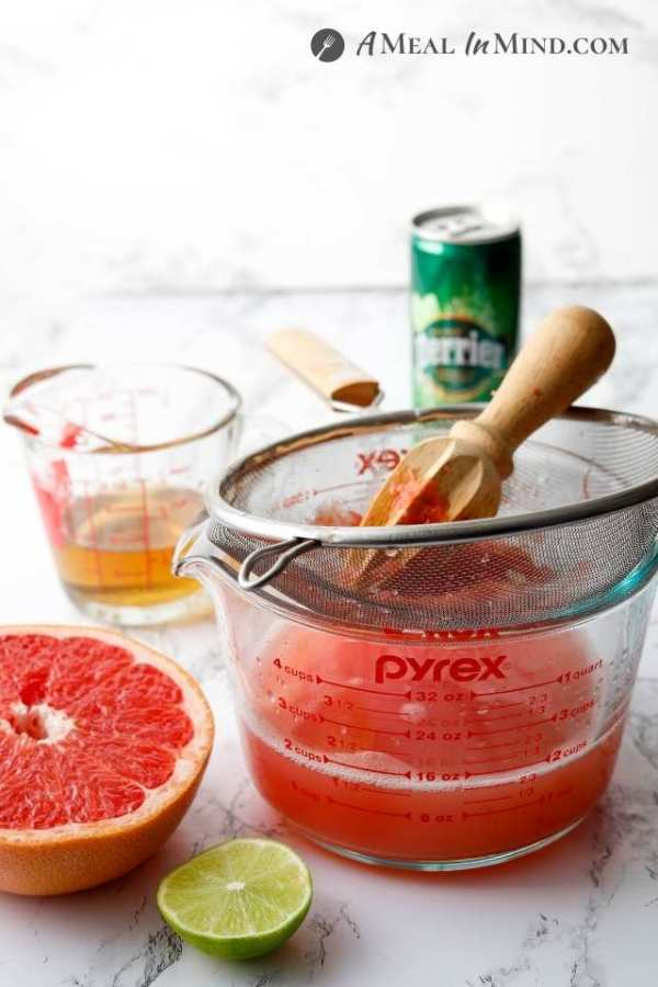 juicing grapefruit into a measuring cup using a reamer and strainer