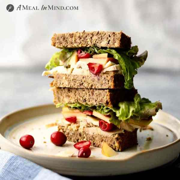 chicken-apple-brie sandwich with cranberries on ivory plate