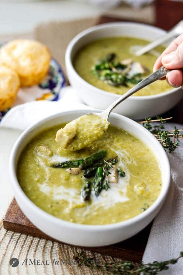 creamy asparagus soup in white bowls with spoons side view