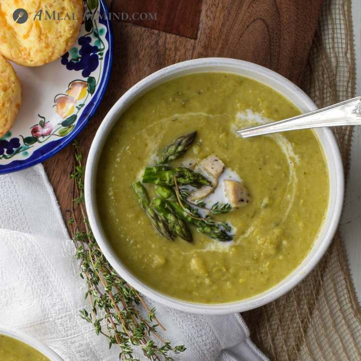 bowl of creamy asparagus soup with garnishes and spoon