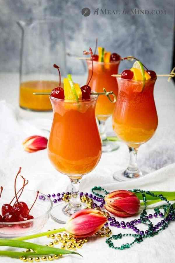 three hurricane mocktails with garnishes and mardi gras beads on white cloth