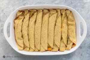 rolled carne asada enchiladas in white baking dish