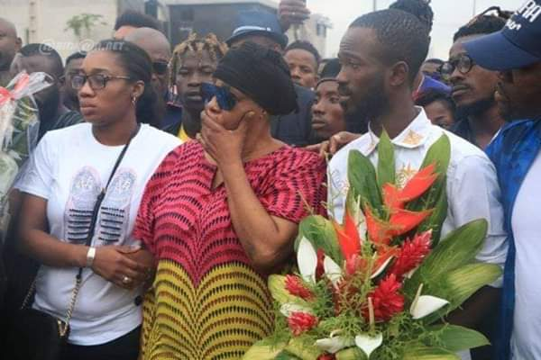 DJ Arafat Mother Visits Accident Scene, Pays Tribute With Flowers