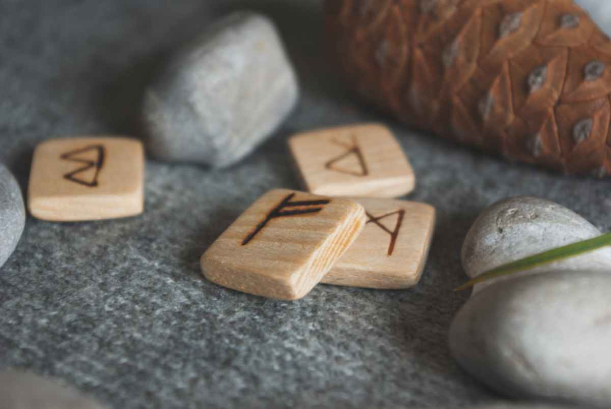 wooden runes and stones scattered on wool plaid