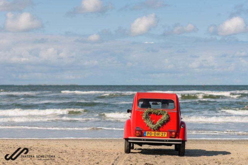 Trouwen in een rode eend op het strand van Ameland