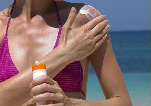 Femme à la plage qui met de la crème solaire