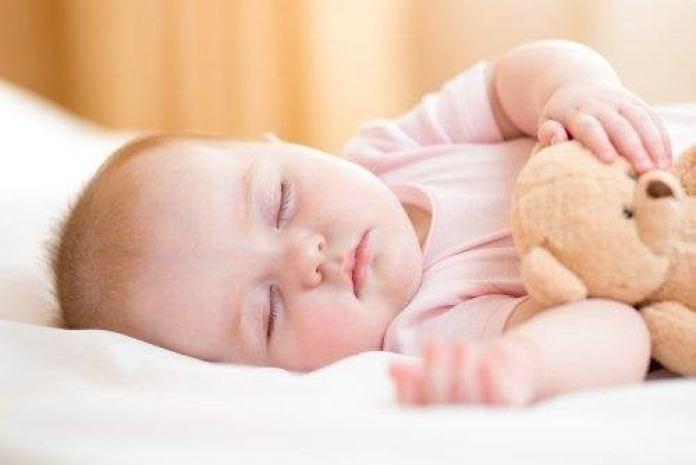 bébé qui dort sur le côté pour calmer les douleurs abdominales