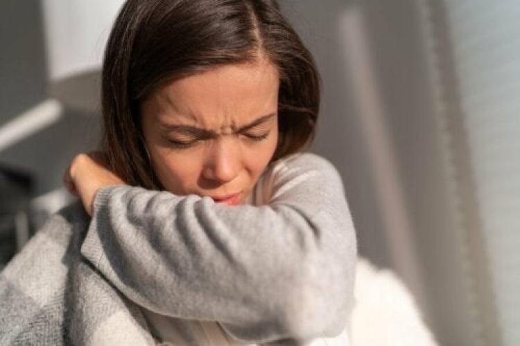 Une femme qui éternue à cause d'une allergie